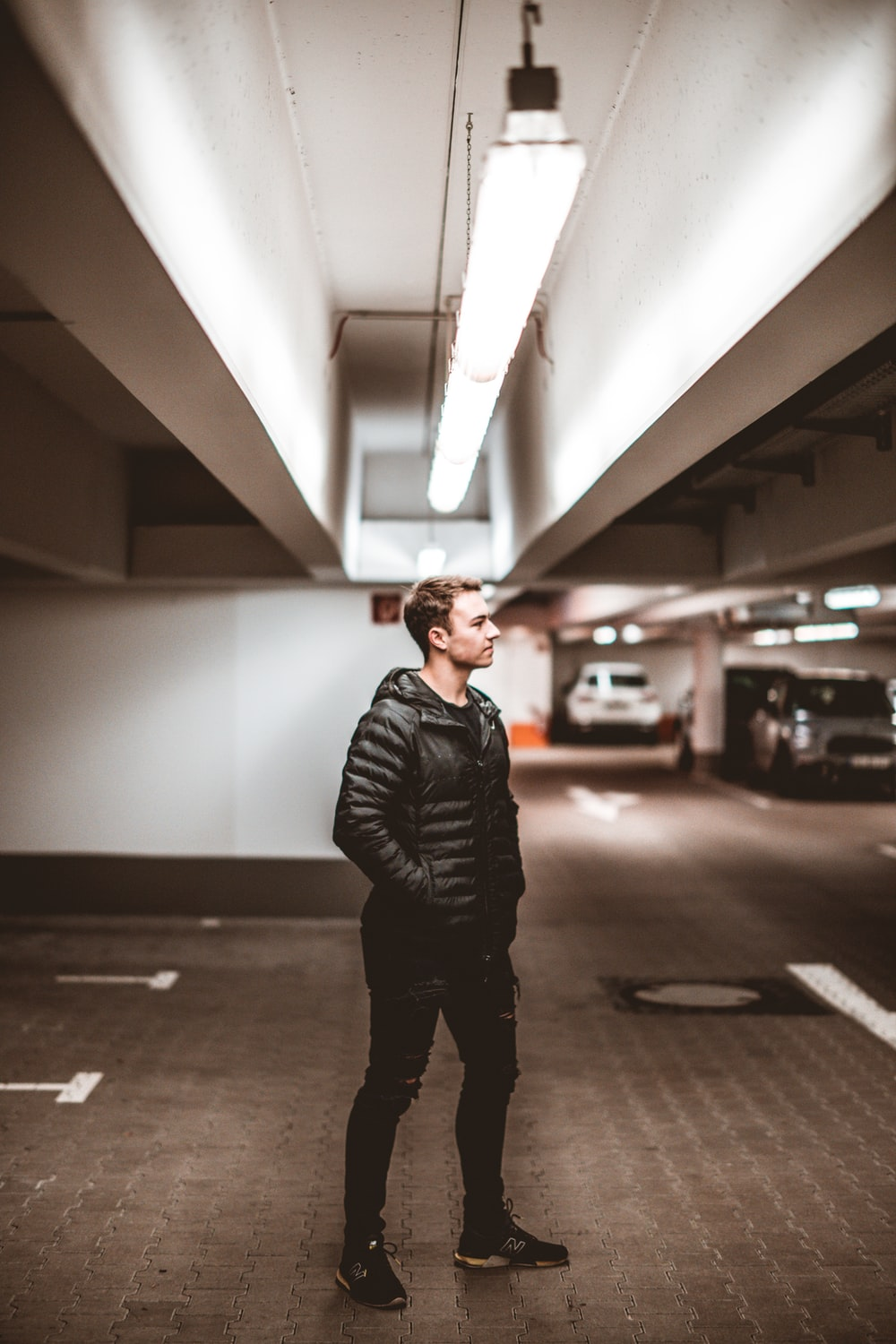 man in black leather jacket standing on hallway