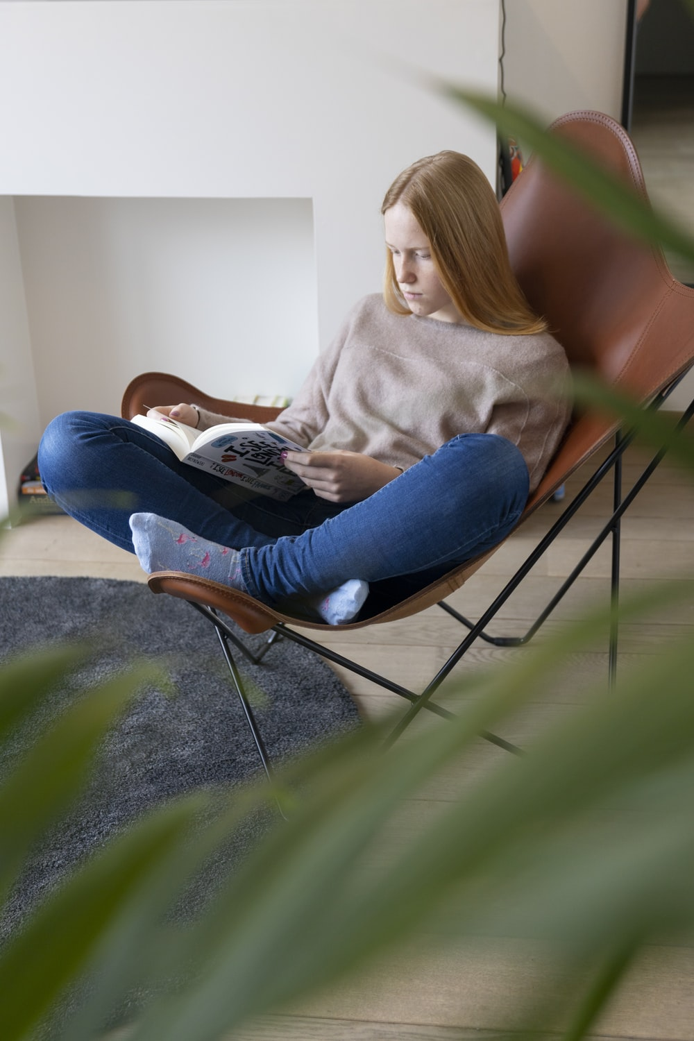 woman in gray sweater and blue denim jeans sitting on gray concrete floor