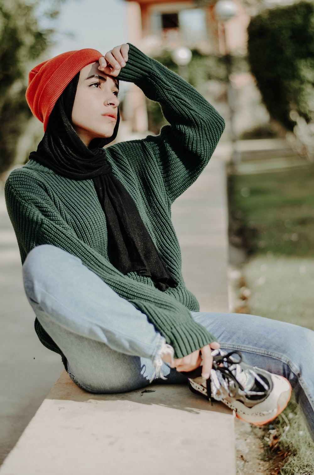woman in green and black hijab and blue denim jeans sitting on concrete bench during daytime