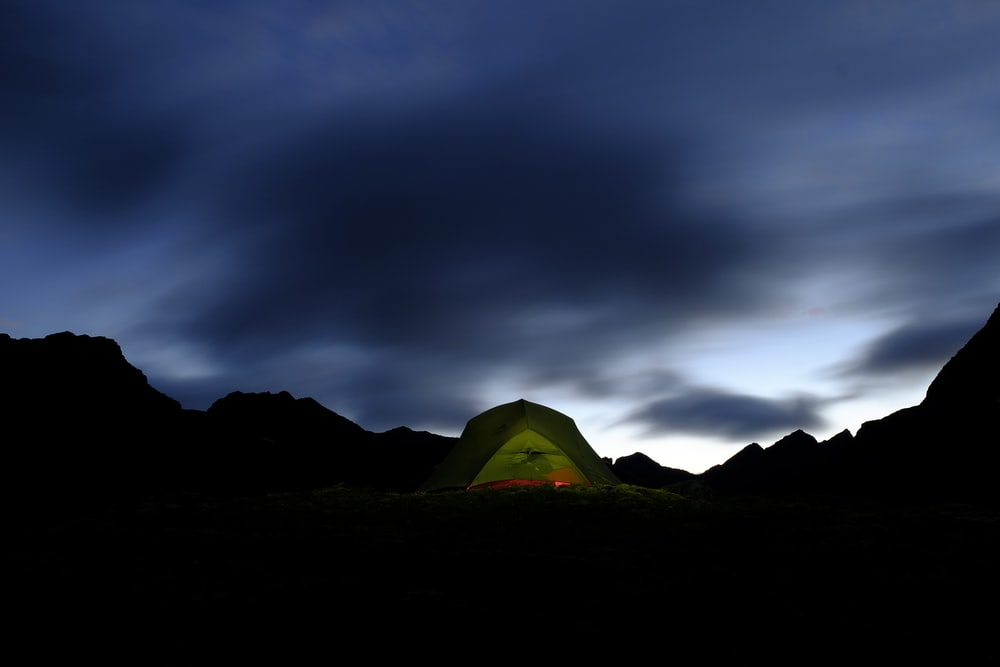 green tent on brown field under gray clouds
