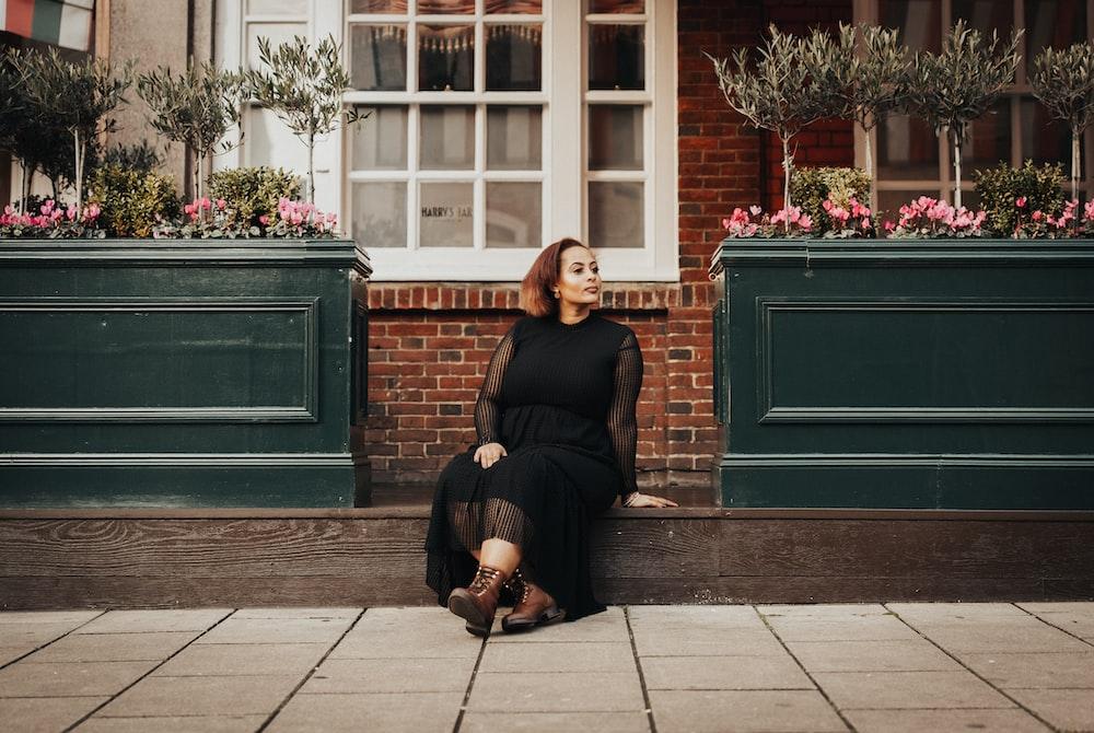 昼間の歩道に座っている黒の長袖シャツの女性
