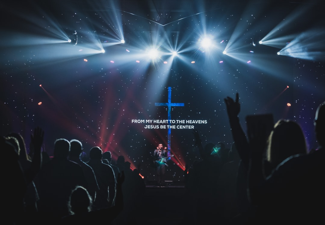 People Standing On Stage With Lights - unsplash