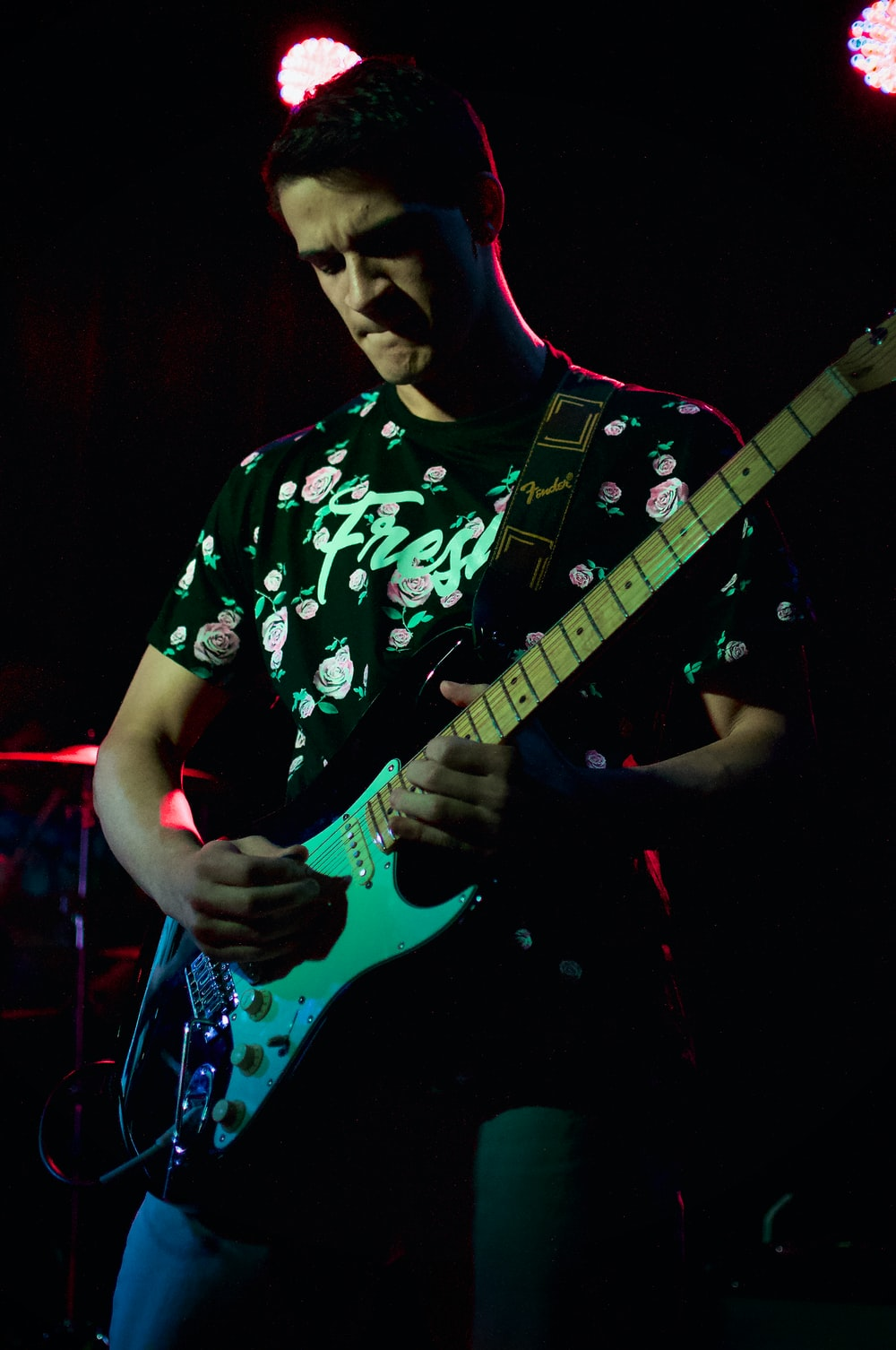 man in black and white floral crew neck t-shirt playing electric guitar