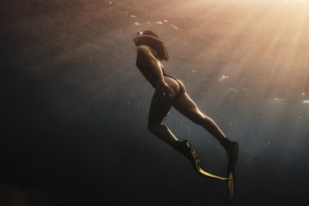 man in black shorts under water