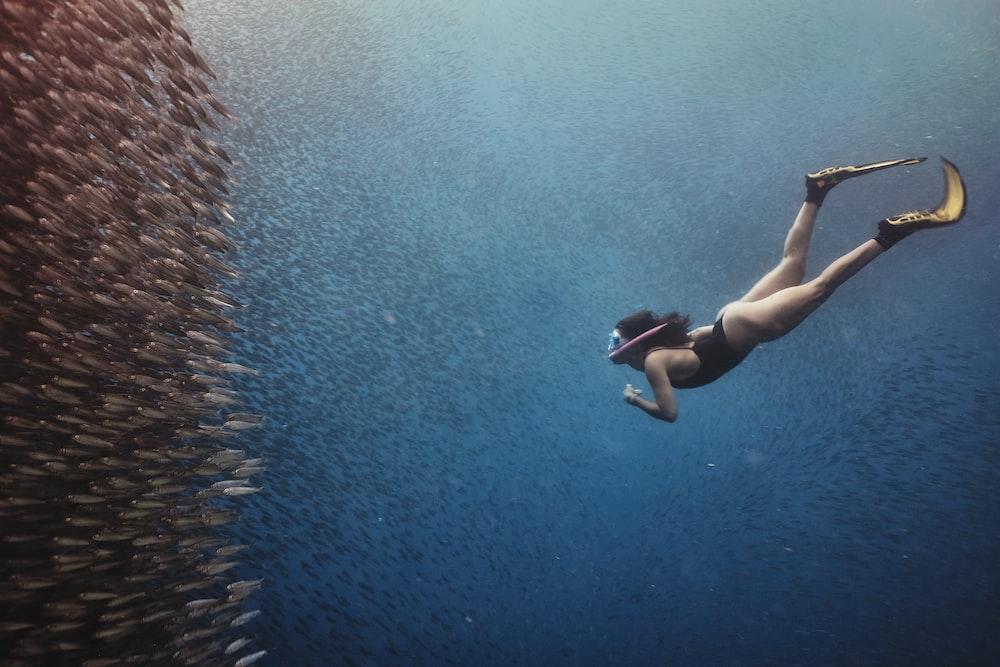 woman in black bikini swimming on water