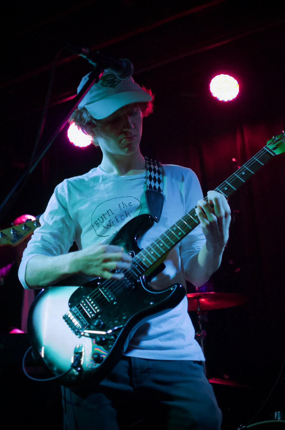 man in white and black crew neck t-shirt playing electric guitar