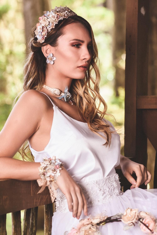 woman in white sleeveless dress wearing white flower crown