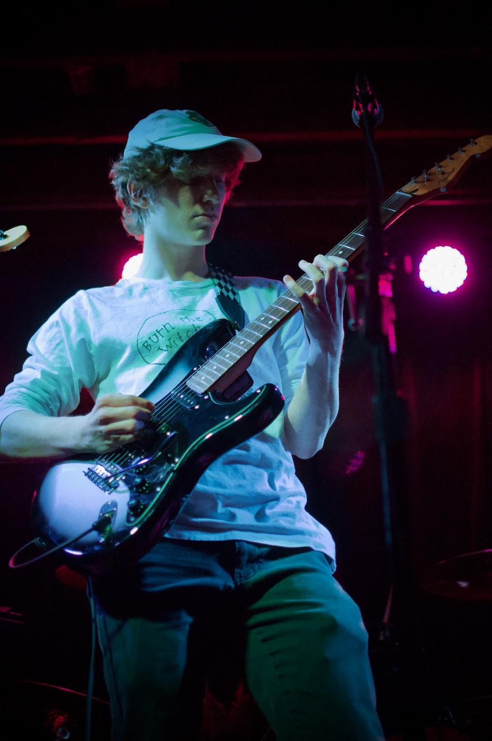 man in white dress shirt playing electric guitar