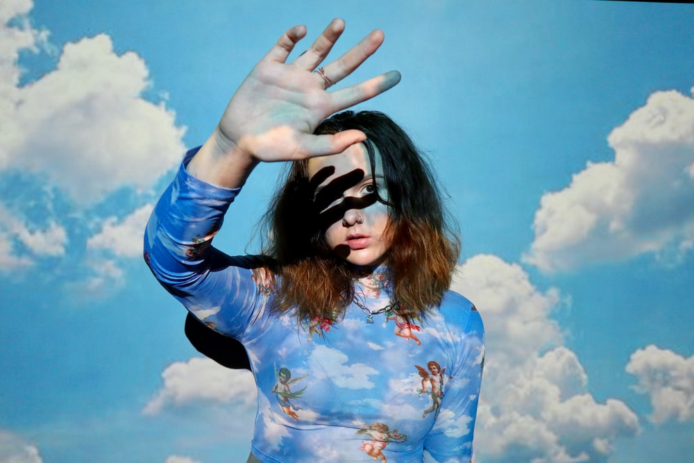 woman in blue and white floral long sleeve shirt wearing black sunglasses