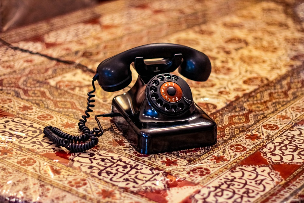 black rotary telephone on brown and white textile