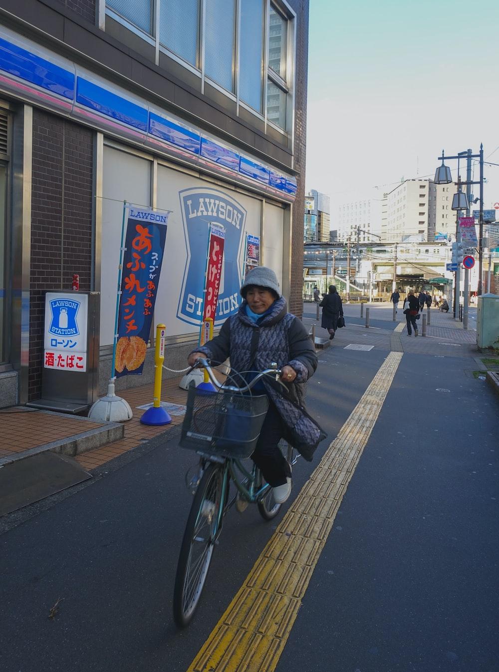 man in black jacket riding bicycle on sidewalk during daytime