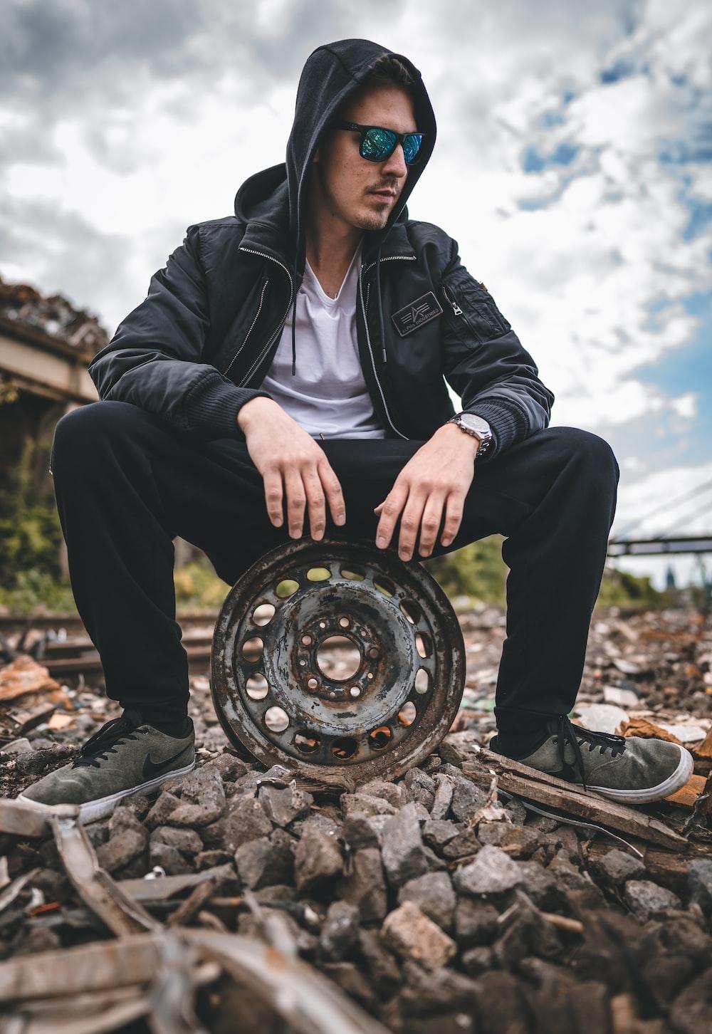 man in black leather jacket and black pants sitting on brown metal wheel during daytime