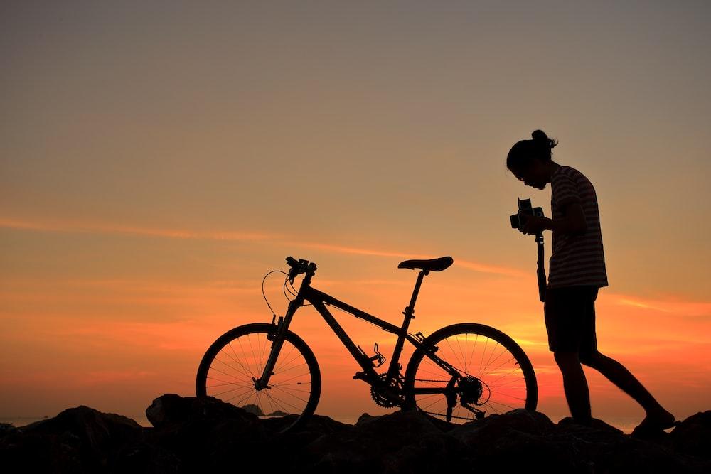 silhouette of man standing beside black mountain bike during sunset