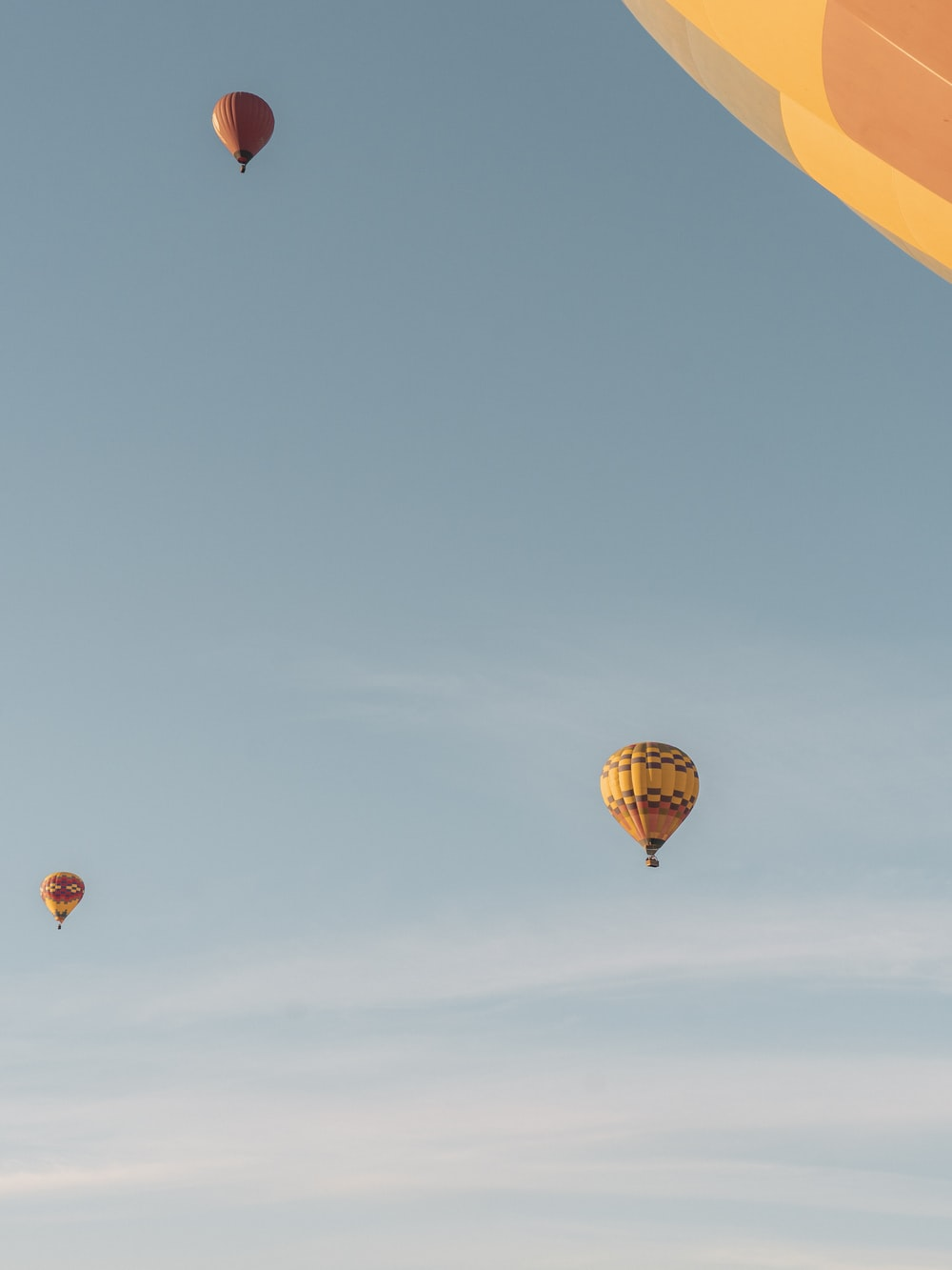 red and yellow hot air balloon in mid air under blue sky during daytime