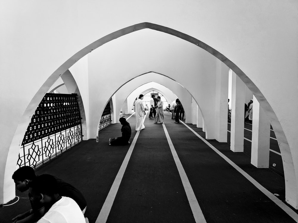 grayscale photo of man in white shirt walking on hallway