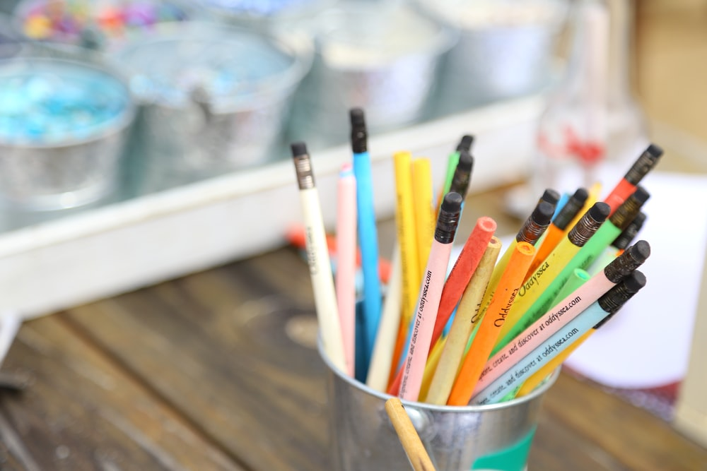 assorted color pencils in white plastic cup