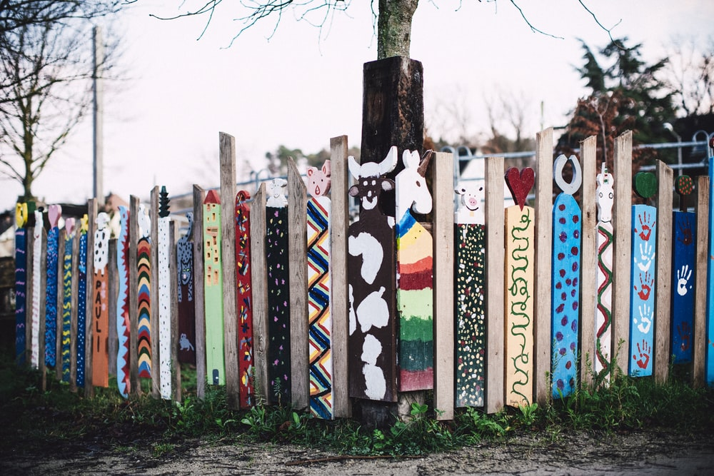 multi colored wooden fence near trees during daytime