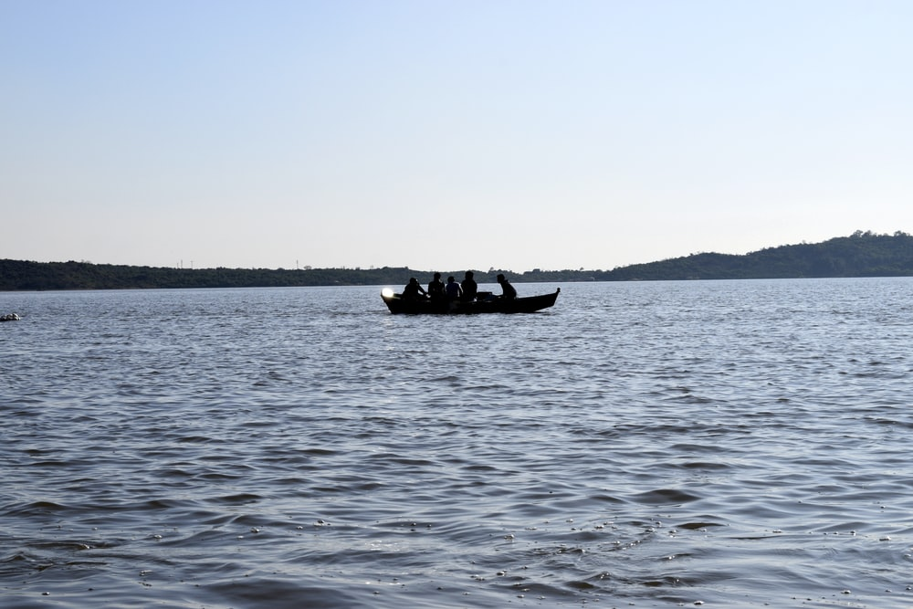 silhouette of person riding on boat on sea during daytime