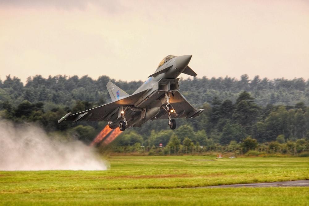 black jet plane on green grass field during daytime