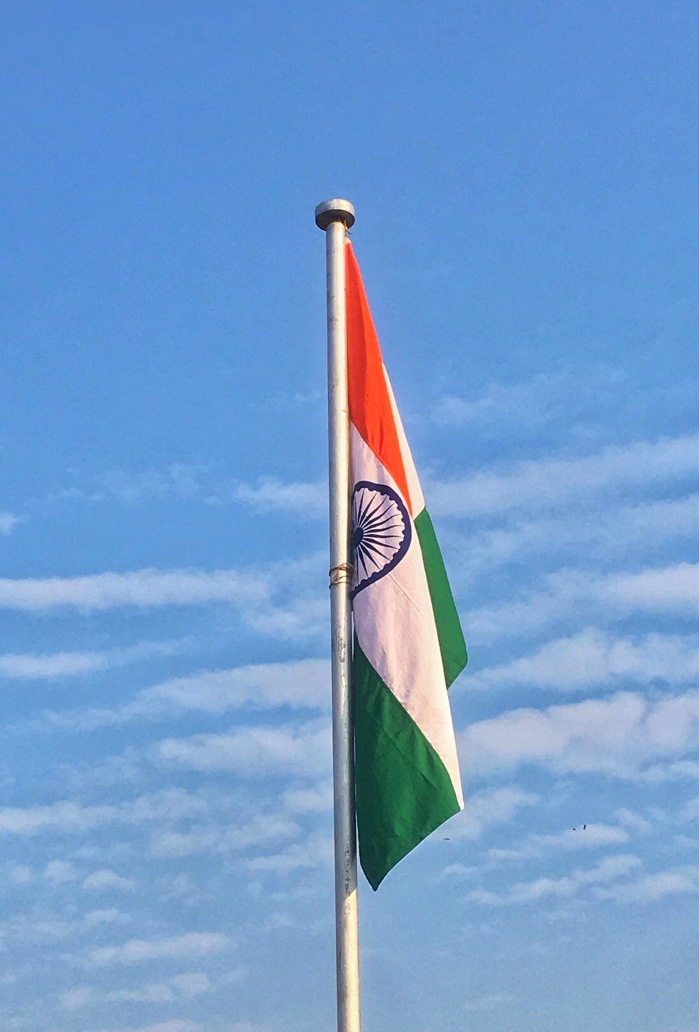 green white and red striped flag under blue sky during daytime