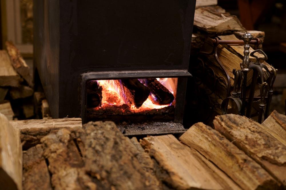 black wood burner near brown firewood