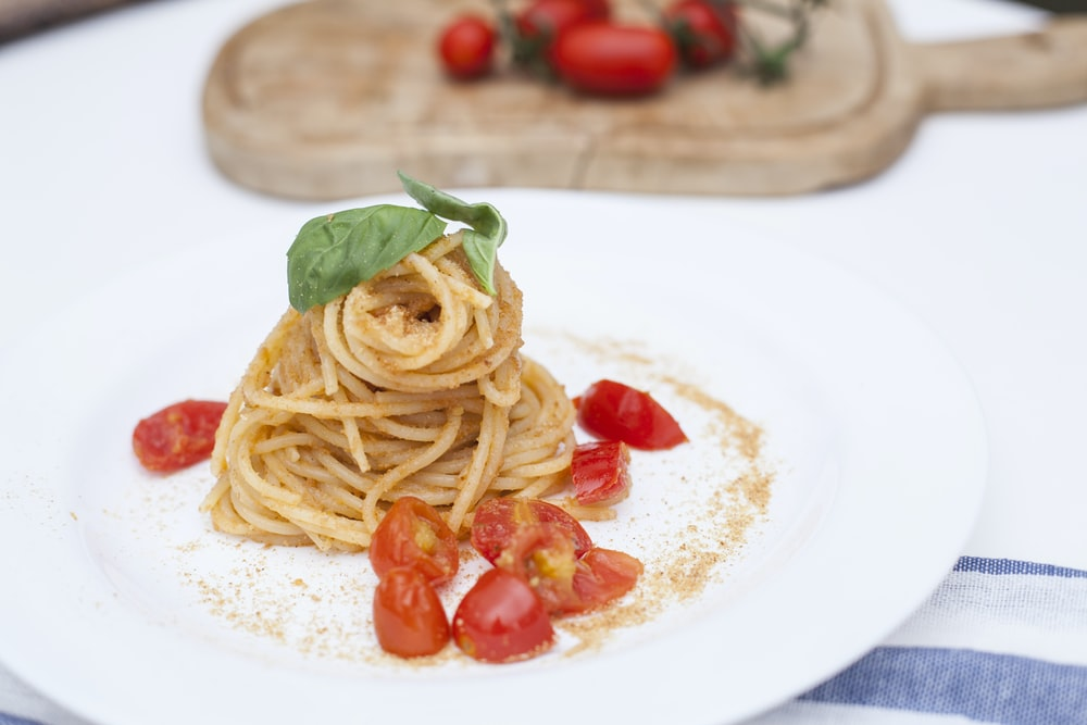 pasta with red tomato on white ceramic plate
