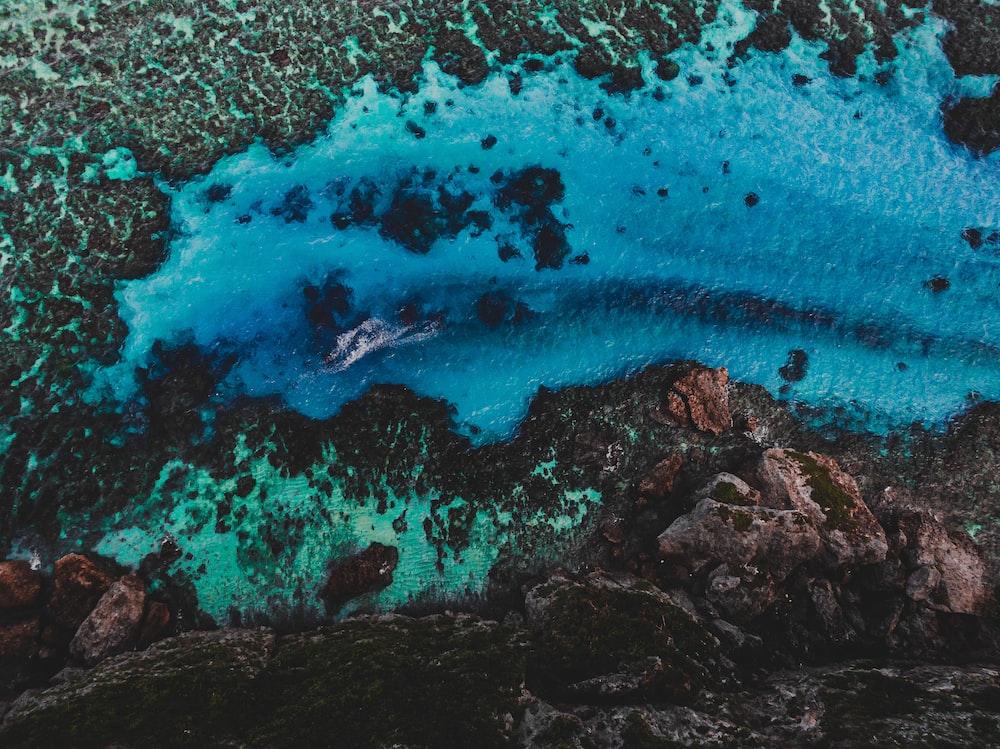 aerial view of ocean waves crashing on rocks