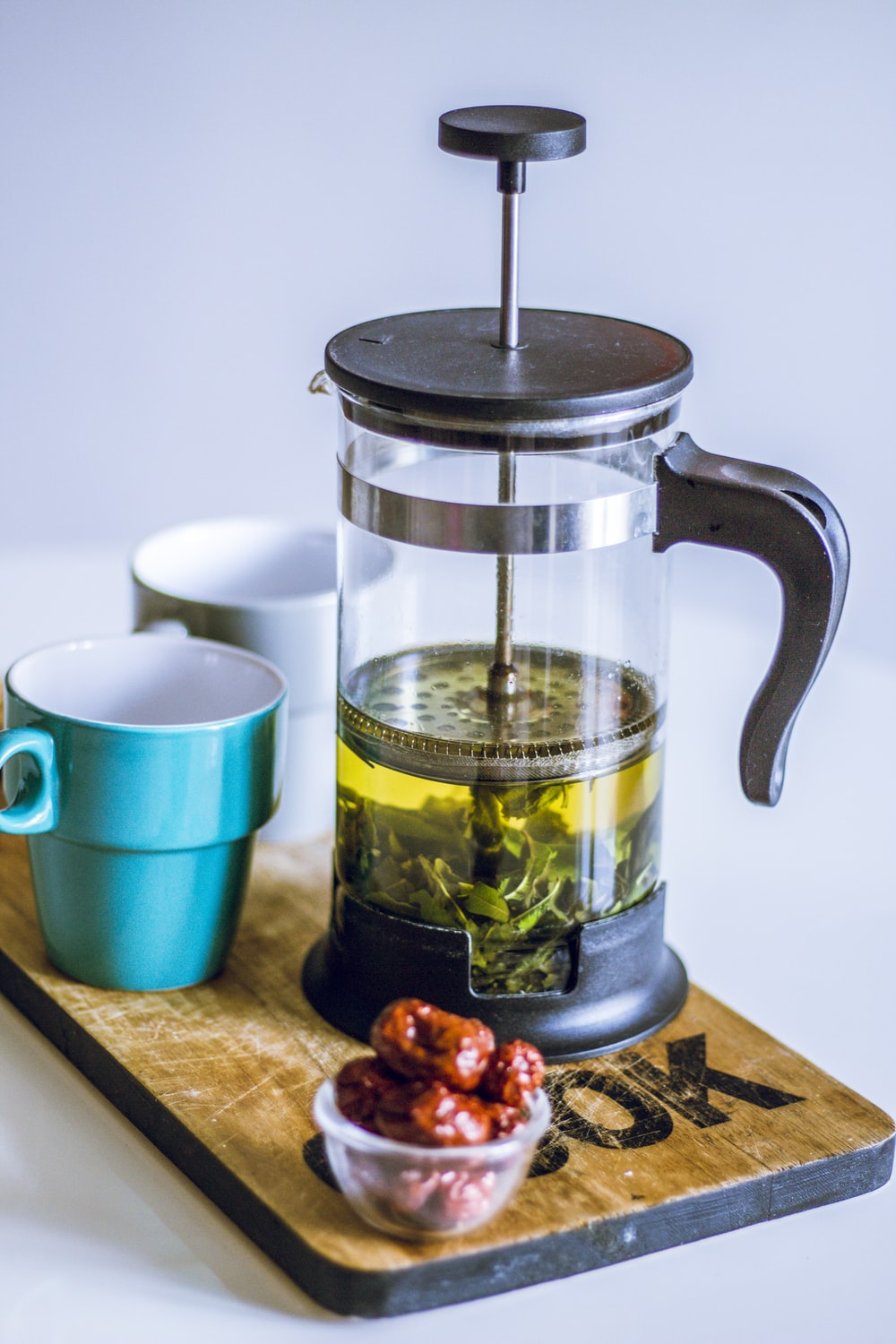 silver and black coffee press beside blue ceramic mug on brown wooden chopping board