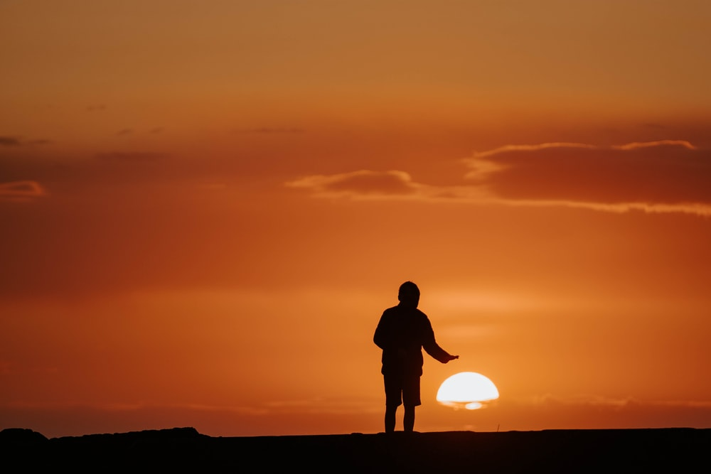 silhouette of man standing on hill during sunset