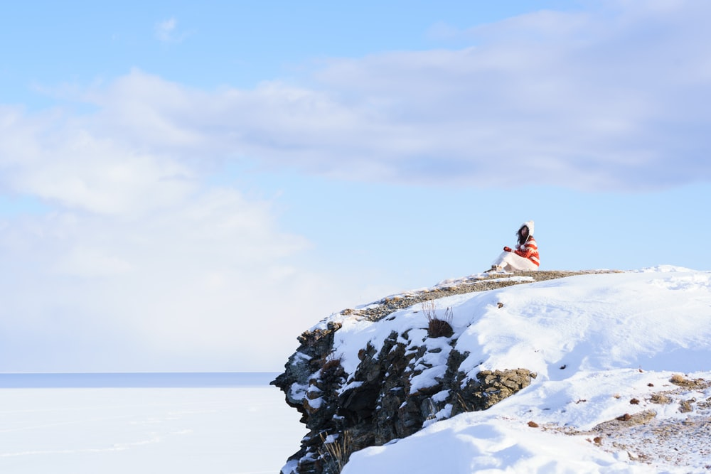 woman in pink jacket sitting on snow covered ground during daytime