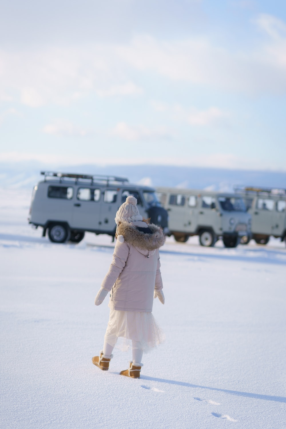 woman in white dress standing on snow covered ground during daytime