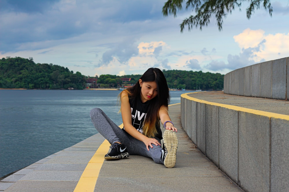 woman in black tank top and gray pants sitting on concrete dock during daytime