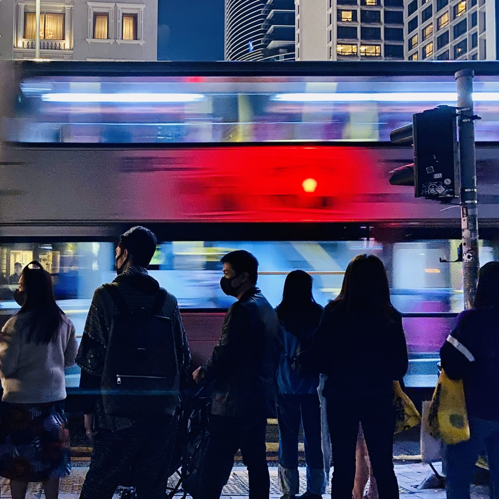 people standing in front of red and white train during night time
