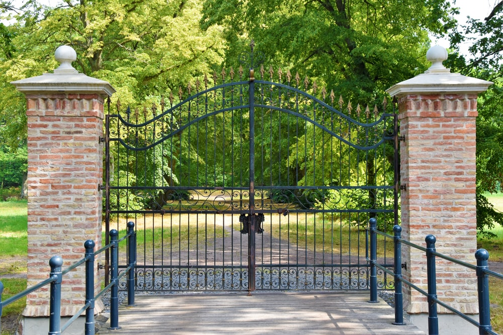 black metal gate near green trees during daytime