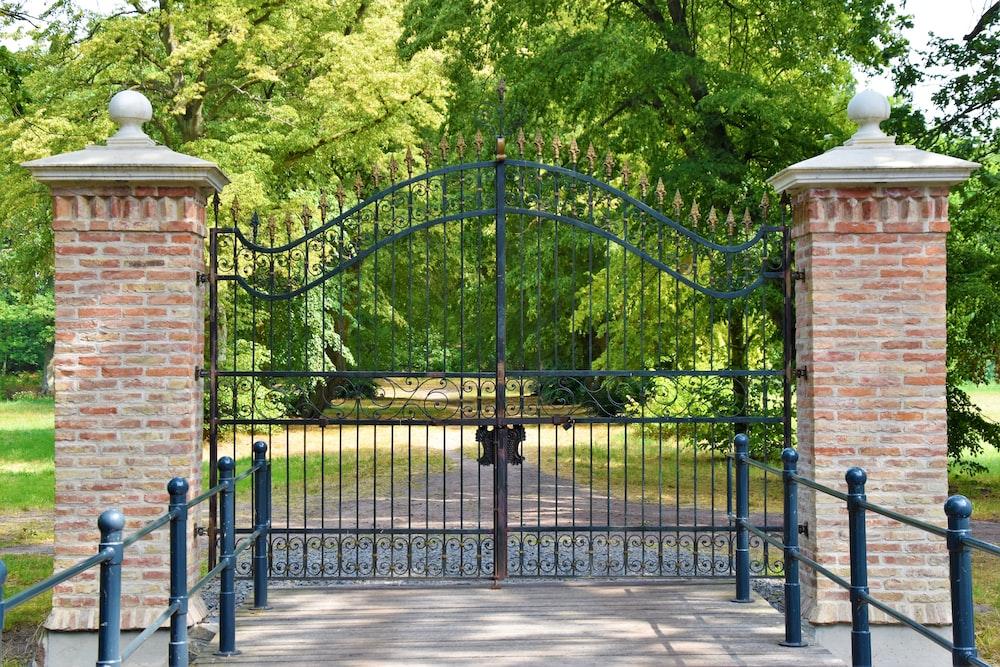 black metal gate near green trees during daytime
