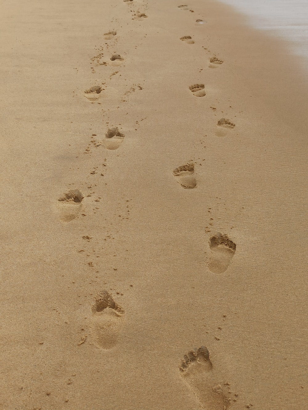 footprints on the sand during daytime