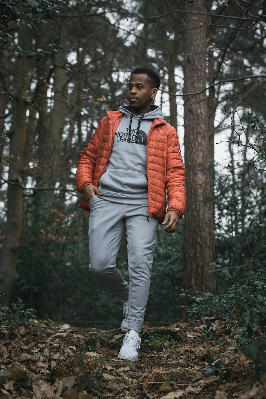 man in orange zip up jacket standing near trees during daytime