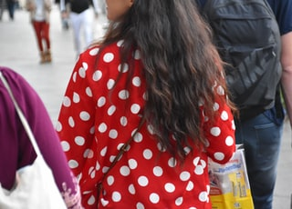 woman in red and white polka dot long sleeve shirt holding plastic bottle
