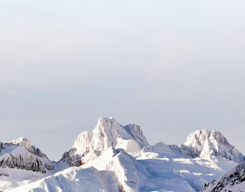 snow covered mountains under gray sky