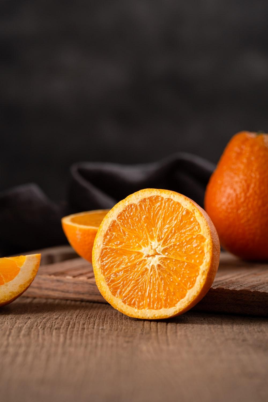 sliced orange fruit on brown wooden table