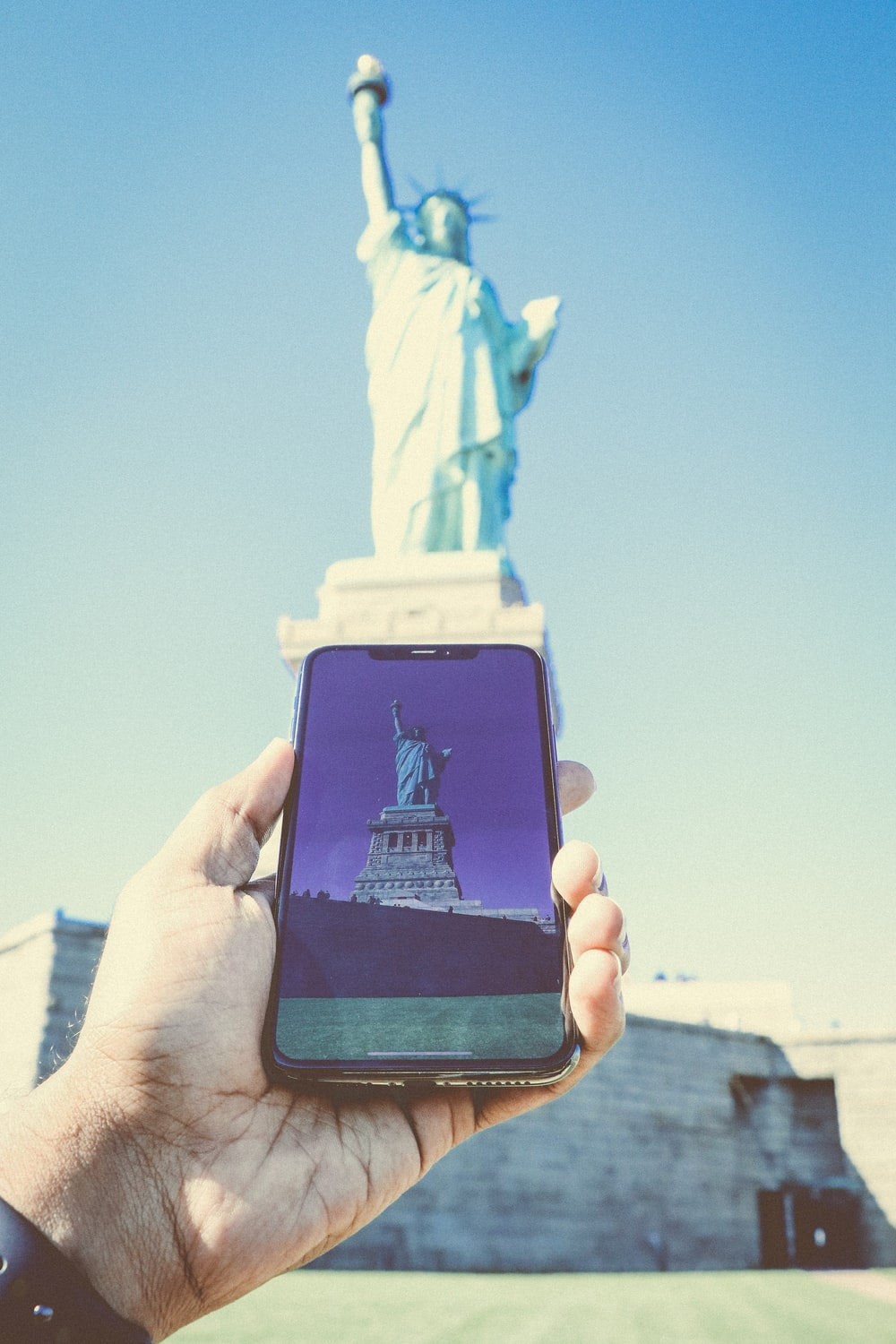 person holding black smartphone taking photo of statue of liberty