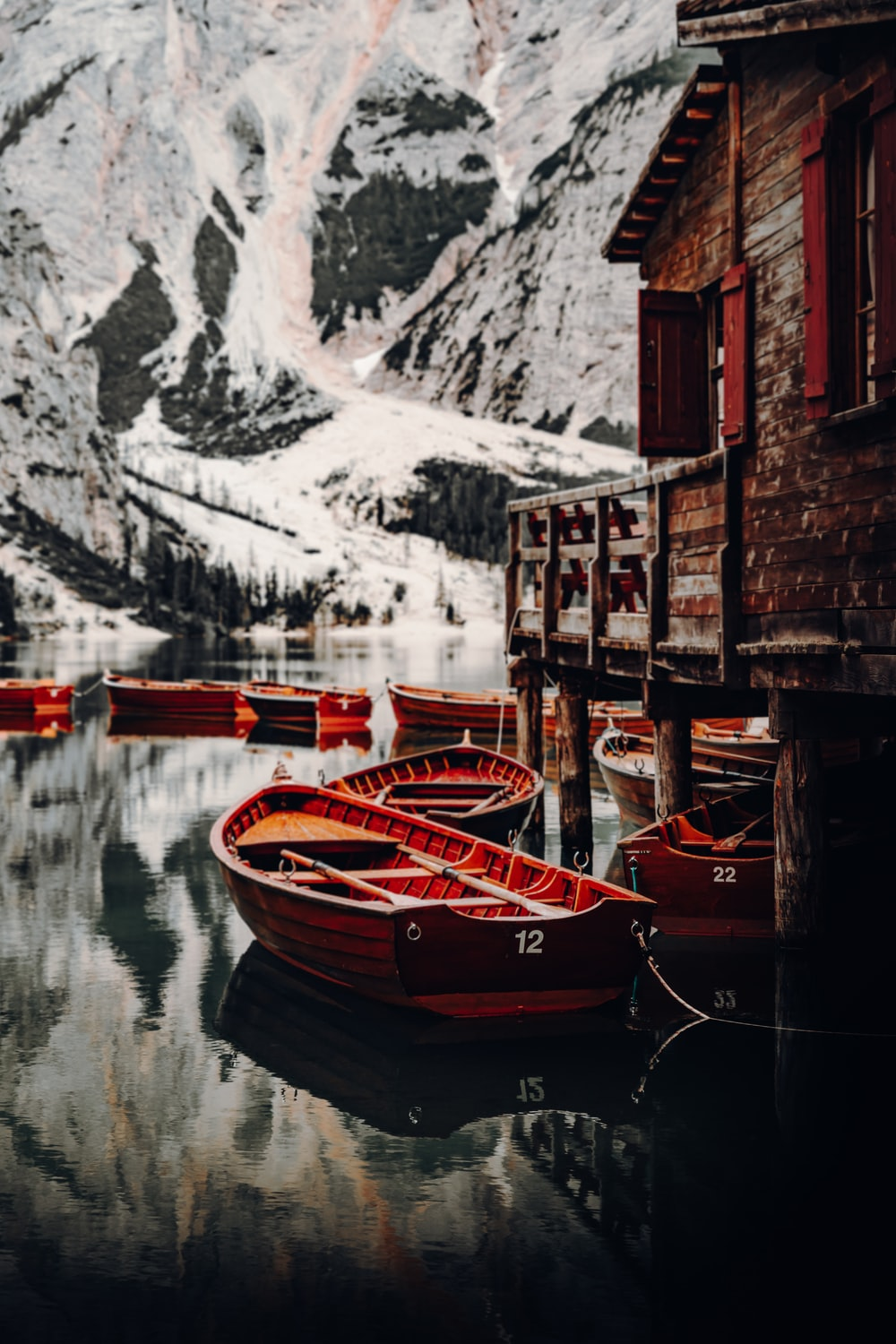brown wooden boat on water near snow covered mountain during daytime