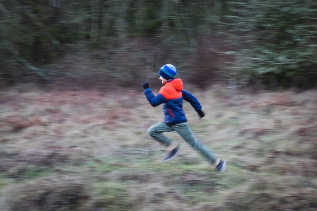 boy running fast in the forest outside during fall or winter