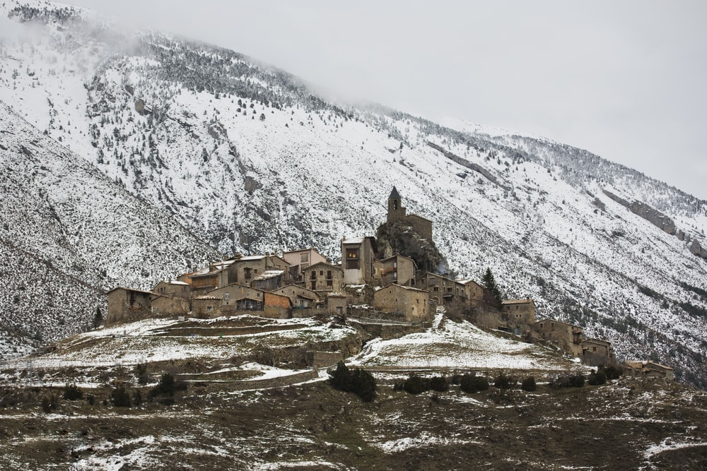 brown concrete houses near snow covered mountain during daytime