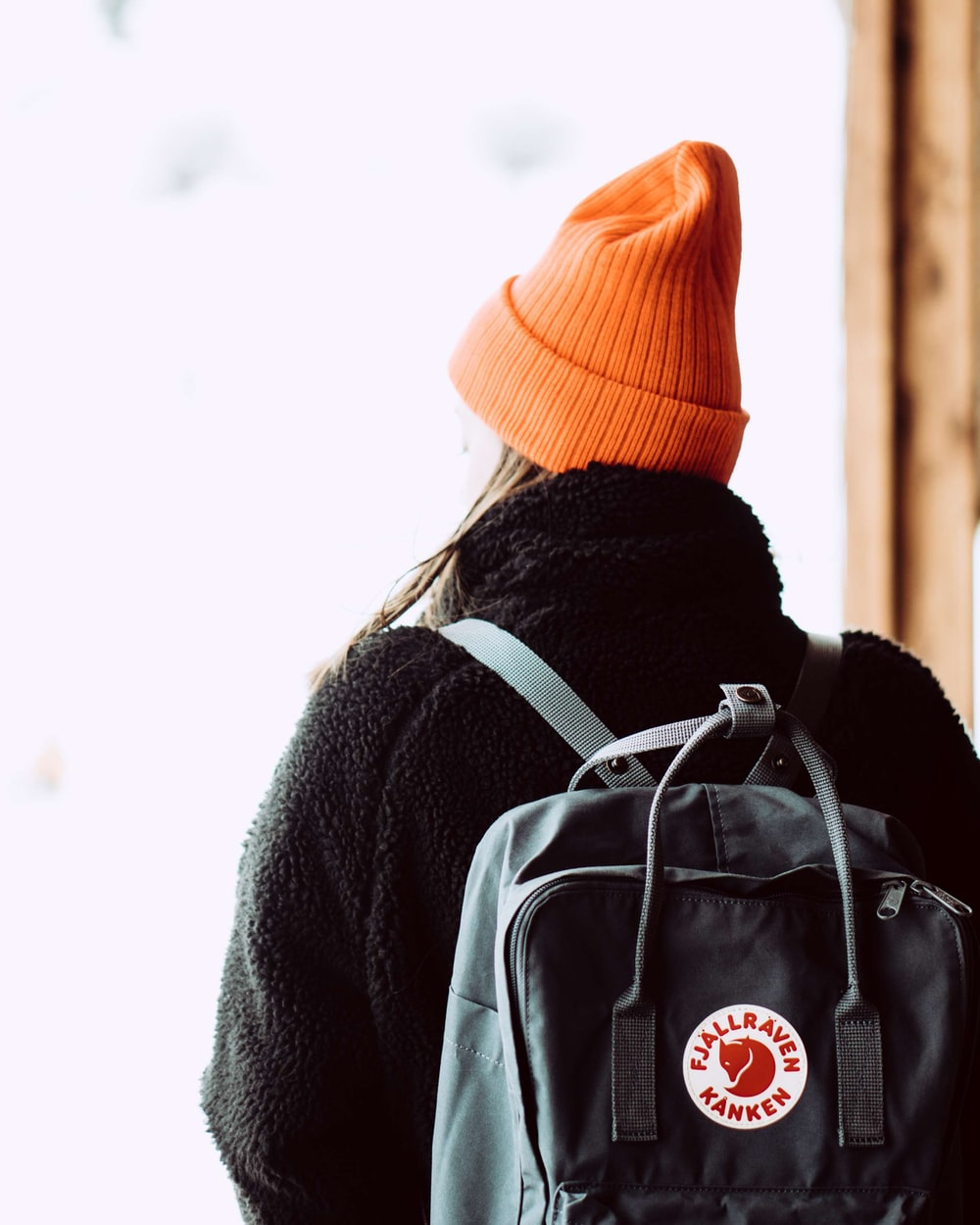 person in gray coat and orange knit cap