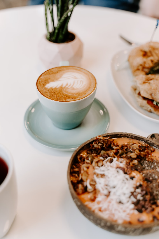 cappuccino in white ceramic cup on white ceramic saucer