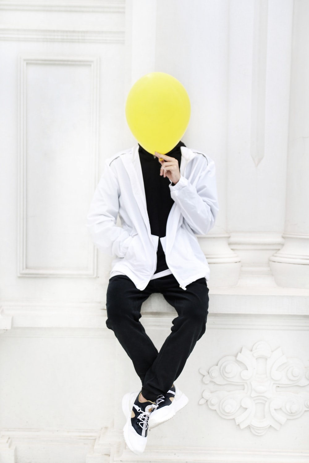 man in white dress shirt holding yellow balloon