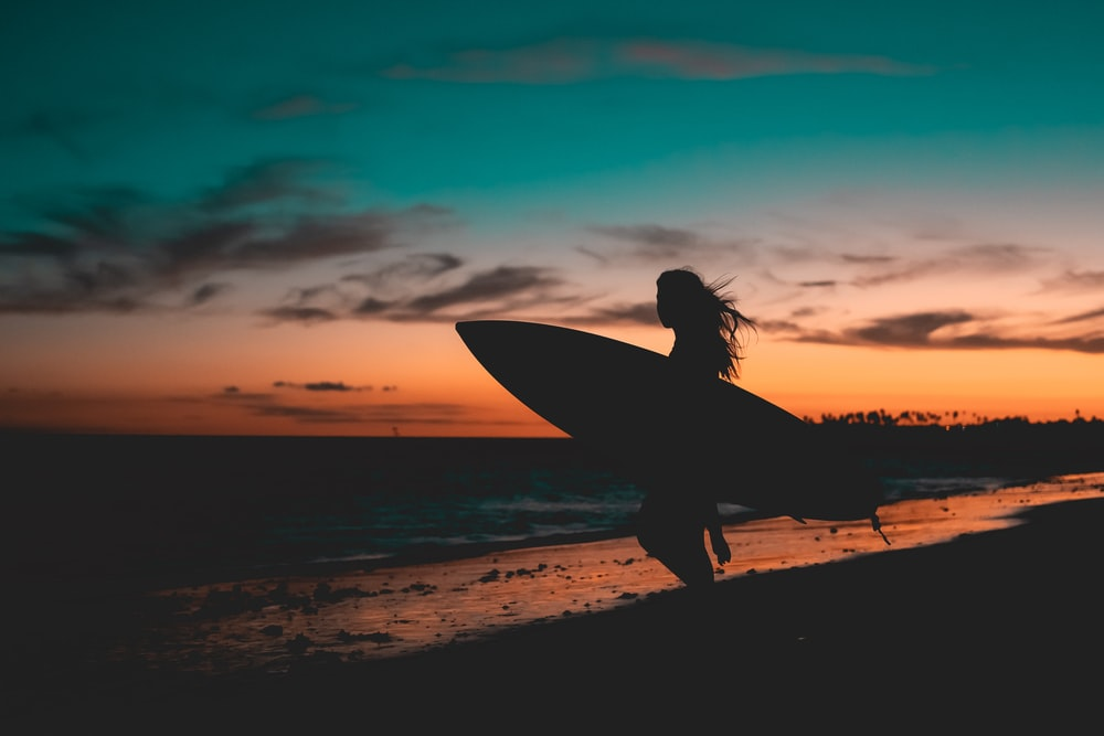 silhouette of woman holding surfboard on beach during sunset