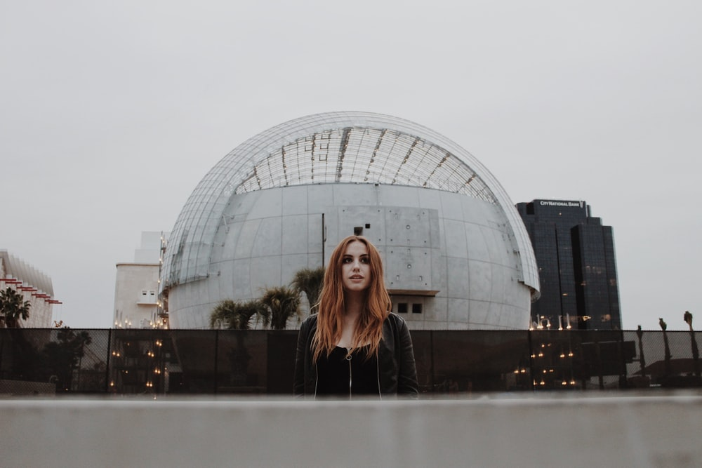 woman in black long sleeve shirt standing near glass building during daytime