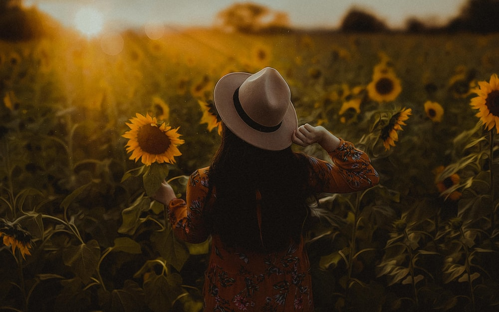 woman in black and red floral dress wearing white fedora hat standing on sunflower field during
